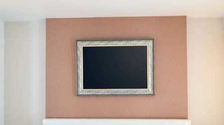 The blank ornate picture frame on the wall