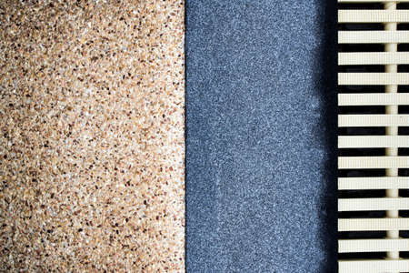 The different surface texture on joint of the exposed aggregate finish flooring and the marble remnants finish flooring and the plastic gutter cover beside the pool