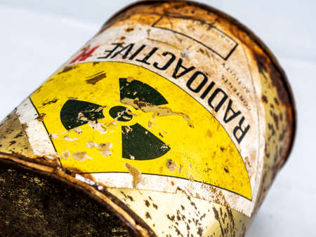 Radiation warning sign on transport index label stick on the rust and decay radioactive material container, Ionizing radiation hazard symbol as background Foto de archivo