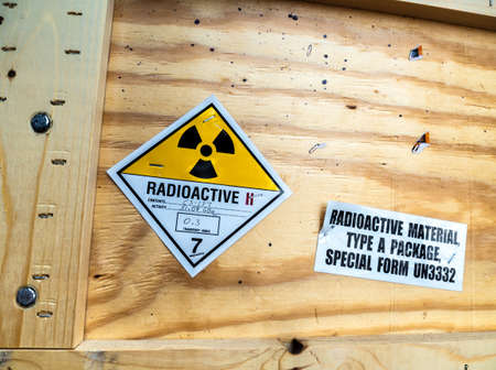 Radioactive material warning label beside the transportation standard wooden package Foto de archivo