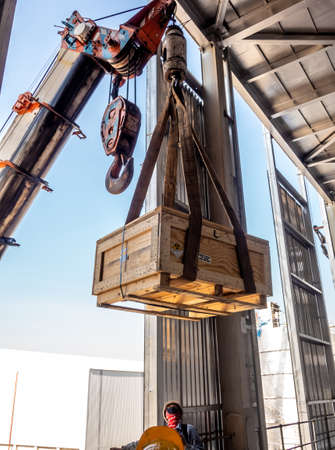 The crane carrying a wooden box of the radioactivity holder into the window on the factory floor