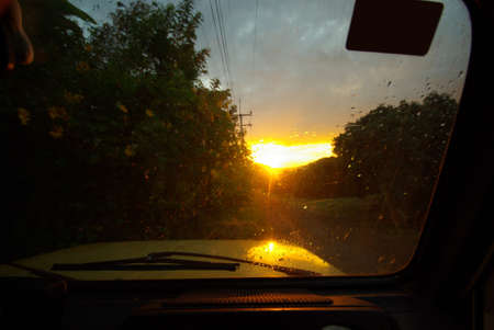 View from the car through the wet windshield after rain on a dirt road and sunlight at dusk