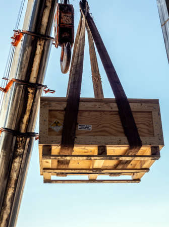 The crane carrying a wooden box of the radioactivity instrument holder transportation wooden box