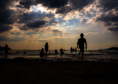 Silhouette in the evening light of people playing in the sea at a public beach