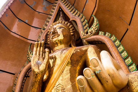 Silver chrysanthemum symbol and gold leaf In the palm of the Buddha statue