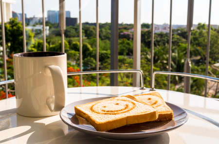 The cup of coffee and some bread breakfast with morning light at the balcony