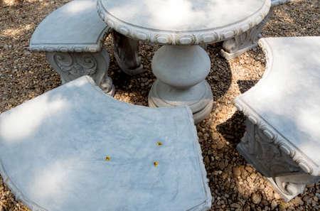 Stucco outdoor table set on the gravel floor in the garden Standard-Bild