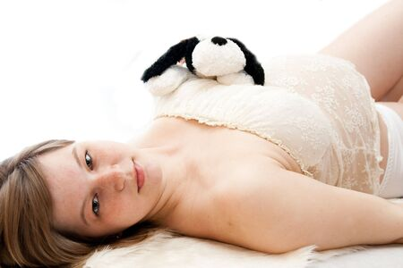 pregnant woman lie on white isolated background photo