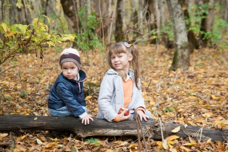 Boy and girl sitting on log photo