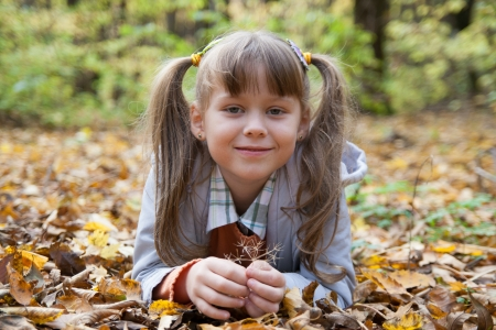 Cute little girl is playing with leaves in autumn park photo