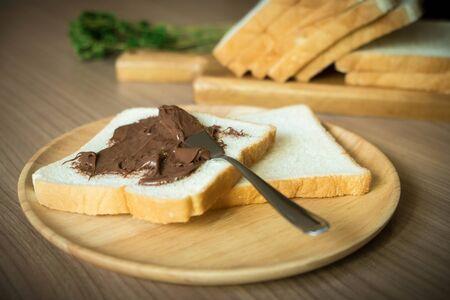 Schokolade ausgebreitet auf Scheibe brot auf der hölzernen Platte. Konzentrierte sich auf das Brot mit der Schokolade, die auf ihm ausgebreitet wurde. Vintage-Ton-Konzept.