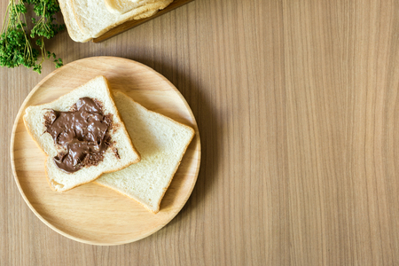 breakfast plate: Chocolate spread on slice of bread on the wood plate. Top view with copy space.