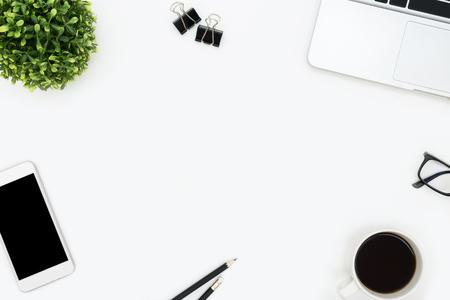 Tavolo da ufficio bianco con laptop, smartphone, caffè e forniture. Vista dall'alto con copia spazio, piatto.