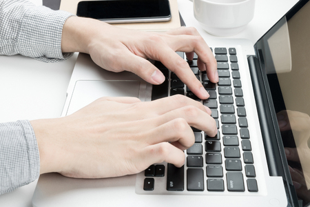Businessman is typing on laptop keyboard. Imagens