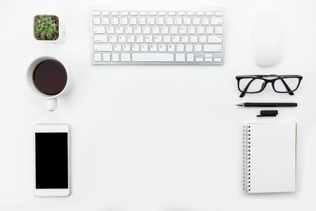 Tavolo da ufficio moderno bianco con gadget e forniture per computer. Vista dall'alto con copia spazio, piatto.