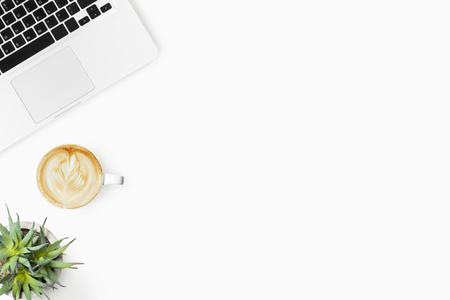 Tavolo da ufficio bianco con computer portatile e tazza di caffè latte. Vista dall'alto con copia spazio, piatto.