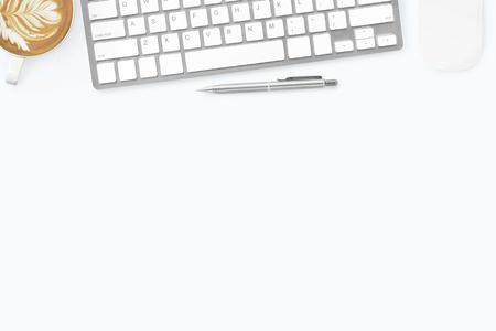 Weißer, minimalistischer Schreibtisch mit Computertastatur, Maus, Latte-Kaffee und Stift. Draufsicht mit Kopienraum, flache Lage. Standard-Bild