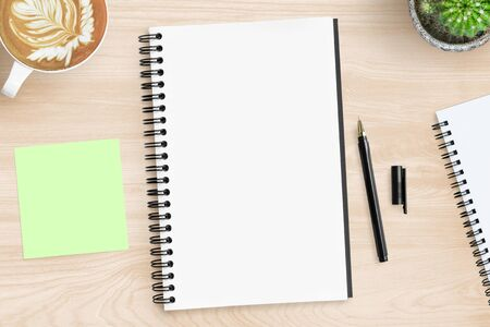 Blank notebook page is on top of wood office desk table with supplies. Top view, flat lay.