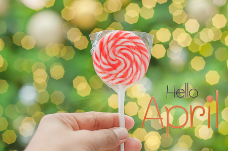 Hello april, Hand holding of red lollipops candy stick on gold and green bokeh background 版權商用圖片