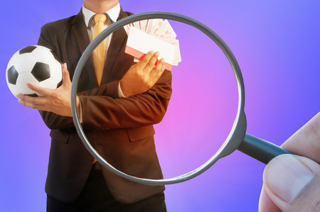 Double exposure of Magnifier searching and Business holding football on  Purple abstract background