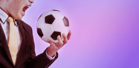 Double exposure of Business holding football Purple abstract background 版權商用圖片