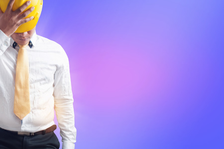 businessman holding hard hat on abstract purple background, copy space