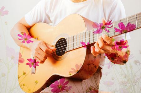 Double exposure of man playing guitar on cosmos flower 版權商用圖片