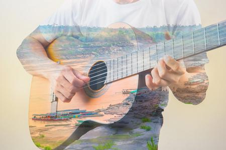 Double exposure of man playing guitar on harbor 版權商用圖片