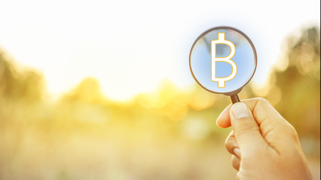 Hand hold magnifying glass of bitcoin on cryptocurrency