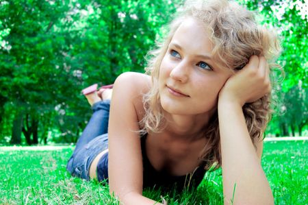 Young beautiful girl lies on the lawn and thinking about the future. photo