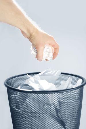 trash basket: Imagen conceptual de la basura. Hombre produce papel en una basura completa.
