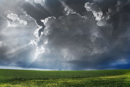 Storm clouds over field with green grass. photo