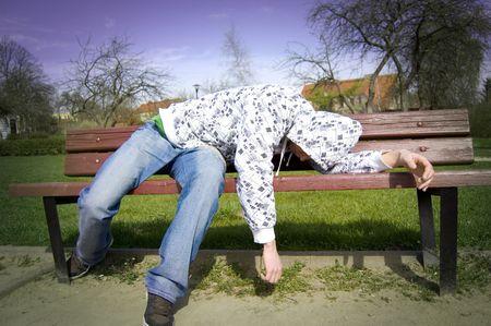 alcoholismo: Un hombre borracho acostado en un banco del parque.  Foto de archivo
