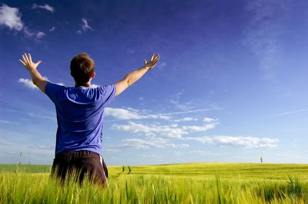 Man standing on the green field at summer and feel the freedom.