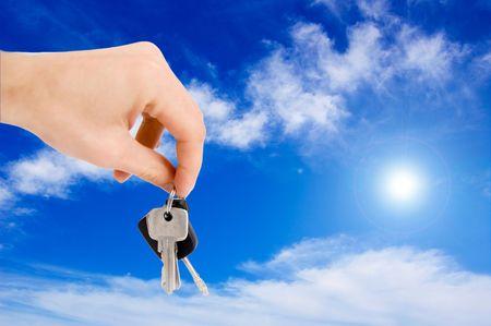 Hand holding keys against blue sky. photo