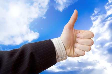 Success in business conceptual image. Businessman hand against the blue sky. photo