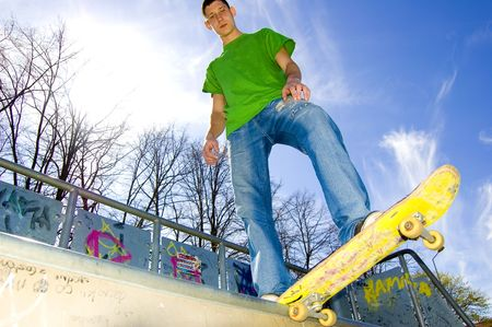 Sport conceptual image.  Teenage skateboarder standing on the ramp with skateboard.