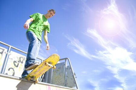 Sport conceptual image. Teenage skateboarder standing on the ramp with skateboard. photo