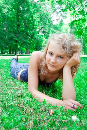 Young beautiful girl lies on the lawn. photo