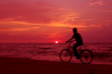 dismounted: Active. Cyclist on the beach at sundown. Stock Photo