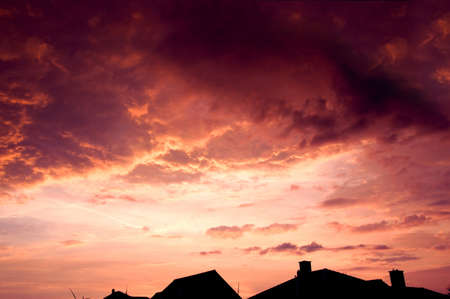 dramatic clouds: Sunset red sky with dark dramatic clouds over houses. Stock Photo