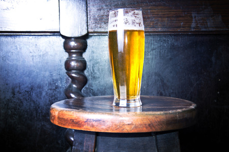 bar chair: Alcohol conceptual image. Glass of fresh cold beer put on the bar chair. Stock Photo