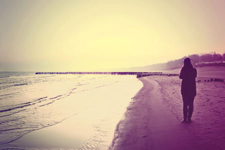 Emotion conceptual image. Lonely woman walking on the beach.