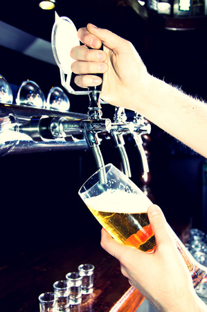 hands  hour: Bartender giving the beer from dispenser. Alcohol conceptual image. Stock Photo