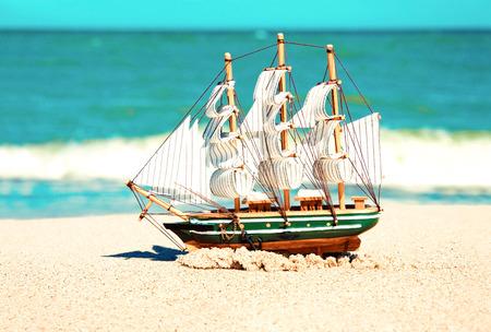 Souvenir conceptual image. Model of ship in the sand near the ocean. Standard-Bild