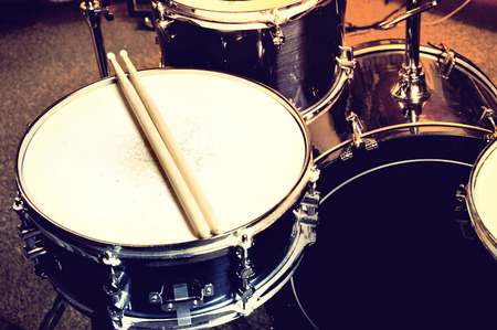 drum and bass: Drums conceptual image. Picture of drums and drumsticks lying on snare drum.