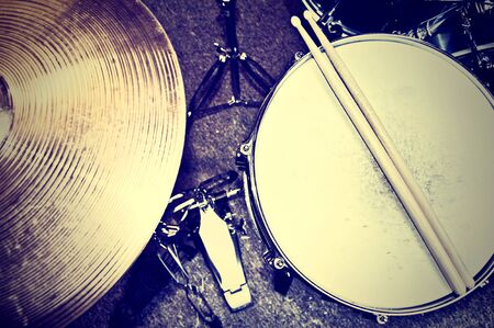 bass drum: Drums conceptual image. Picture of drums and drumsticks lying on snare drum. Retro vintage instagram picture. Stock Photo