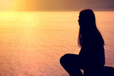 Emotion conceptual image. Lonely young woman on the beach, sitting near ocean.