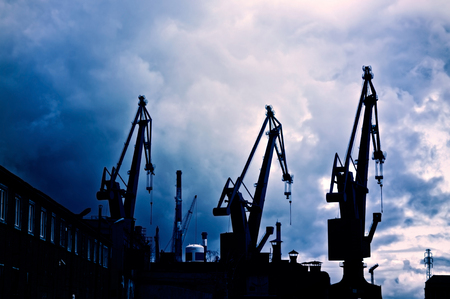 sullen: Industrial conceptual image. Dark and sullen clouds over industrial shipyard area with cranes.