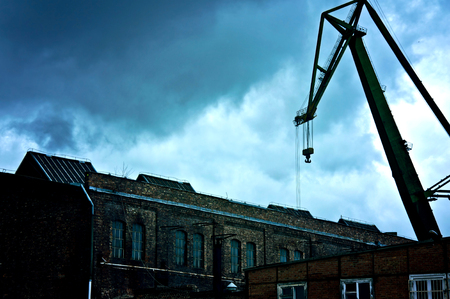sullen: Dark and sullen clouds over old abandoned industrial area with cranes.